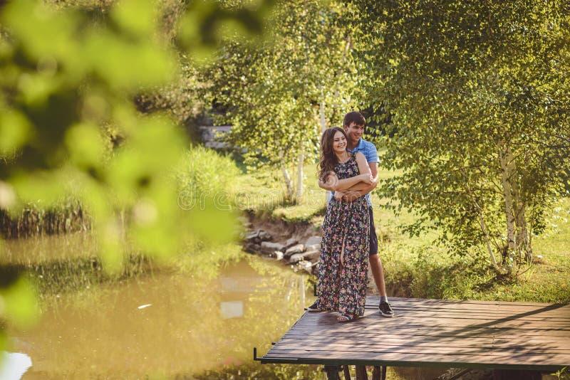Ευτυχές ρομαντικό ζεύγος σε μια ξύλινη γέφυρα κοντά στη λίμνη Ο άνδρας αγκαλιάζει μια νέα γυναίκα, έχουν το γέλιο διασκέδασης στοκ φωτογραφία με δικαίωμα ελεύθερης χρήσης