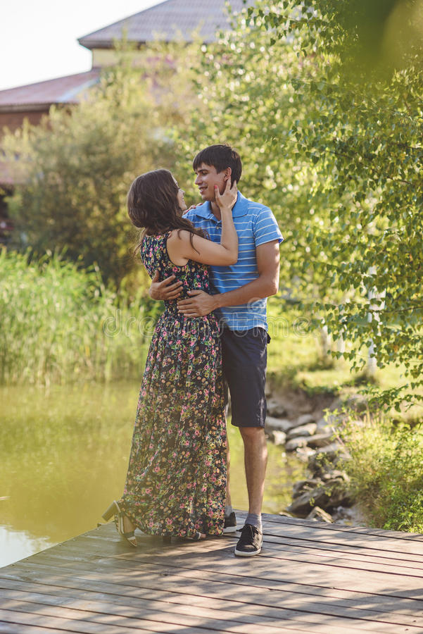 Ευτυχές ρομαντικό ζεύγος στο χωριό, περίπατος στην ξύλινη γέφυρα κοντά στη λίμνη Νέο όμορφο αγκάλιασμα γυναικών και ανδρών στοκ φωτογραφία με δικαίωμα ελεύθερης χρήσης