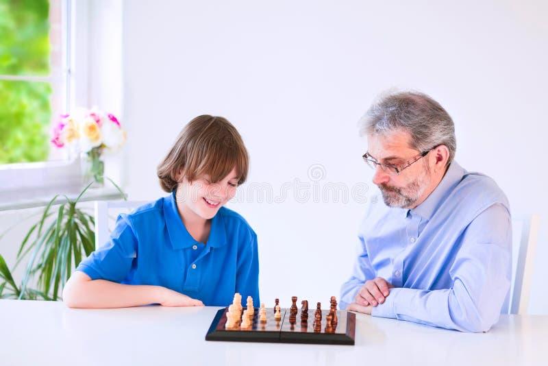 Ευτυχές σκάκι παιχνιδιού παππούδων με το χαριτωμένο εγγονό του στοκ φωτογραφία με δικαίωμα ελεύθερης χρήσης