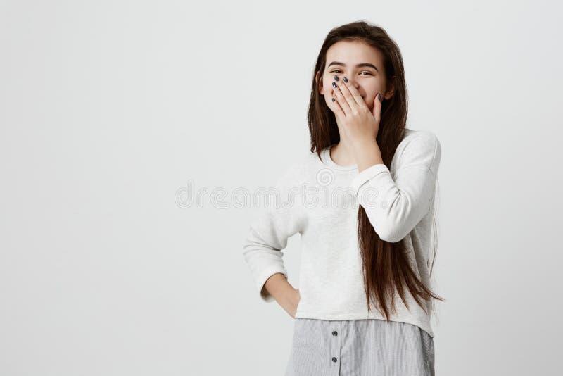 Ευτυχές σκοτεινός-μαλλιαρό κλείνοντας στόμα κοριτσιών με το χέρι που πηγαίνει να δει την έκπληξη που προετοιμάζεται με τη στάση φ στοκ εικόνες