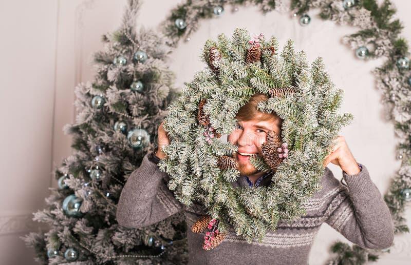 Ευτυχές στεφάνι νεαρών άνδρων και Χριστουγέννων στο σπίτι στοκ εικόνα με δικαίωμα ελεύθερης χρήσης