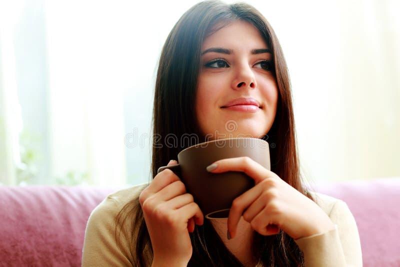 Ευτυχές στοχαστικό φλιτζάνι του καφέ εκμετάλλευσης γυναικών στοκ εικόνες