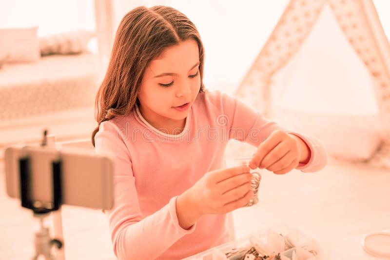 Ευτυχές συμπαθητικό κορίτσι που εξετάζει τα δαχτυλίδια της στοκ εικόνα