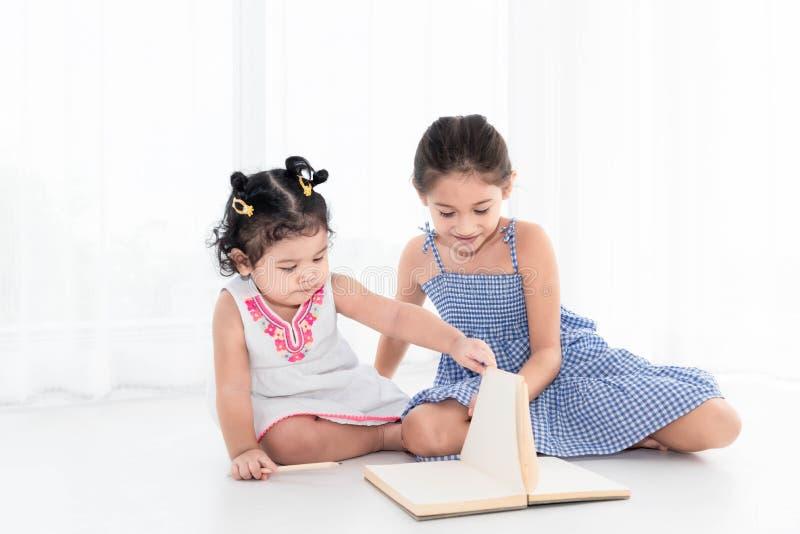 Ευτυχές σχέδιο δύο αδελφών στο βιβλίο σκίτσων μαζί στο σπίτι ή το βρεφικό σταθμό Τρόπος ζωής ανθρώπων και παιχνίδι παιδιών Εκπαίδ στοκ φωτογραφία