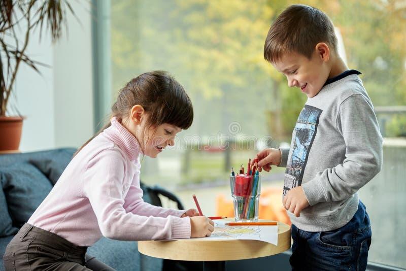 Ευτυχές σχέδιο μικρών κοριτσιών και αγοριών στο σπίτι στοκ εικόνες