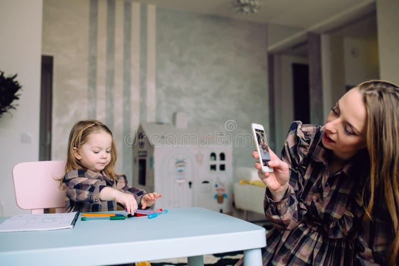 Ευτυχές σχέδιο μικρών κοριτσιών στο σπίτι με το mom στοκ εικόνα με δικαίωμα ελεύθερης χρήσης