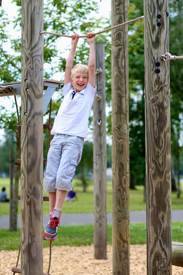 Ευτυχές σχολικό αγόρι που απολαμβάνει την παιδική χαρά στοκ φωτογραφία με δικαίωμα ελεύθερης χρήσης