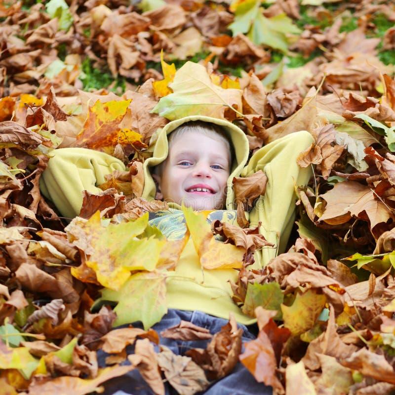 Ευτυχές σχολικό αγόρι στο πάρκο φθινοπώρου στοκ φωτογραφία με δικαίωμα ελεύθερης χρήσης