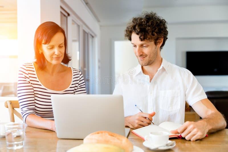 Ευτυχές σύγχρονο ζεύγος που εργάζεται στο lap-top στο σπίτι στοκ εικόνες με δικαίωμα ελεύθερης χρήσης