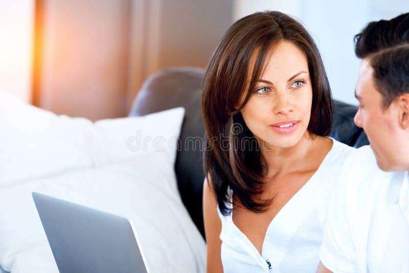 Ευτυχές σύγχρονο ζεύγος που εργάζεται στο lap-top στο σπίτι στοκ εικόνες