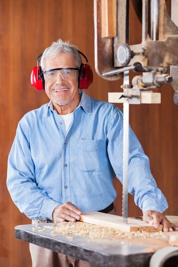 Ευτυχές τέμνον ξύλο ξυλουργών με την πριονοκορδέλλα στοκ εικόνες