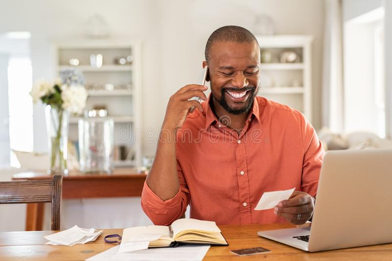 Ευτυχές τιμολόγιο ανάγνωσης ατόμων και ομιλία στο τηλέφωνο στοκ φωτογραφία με δικαίωμα ελεύθερης χρήσης