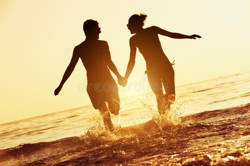 Ευτυχές τρέξιμο θάλασσας ηλιοβασιλέματος ζευγών στοκ εικόνες