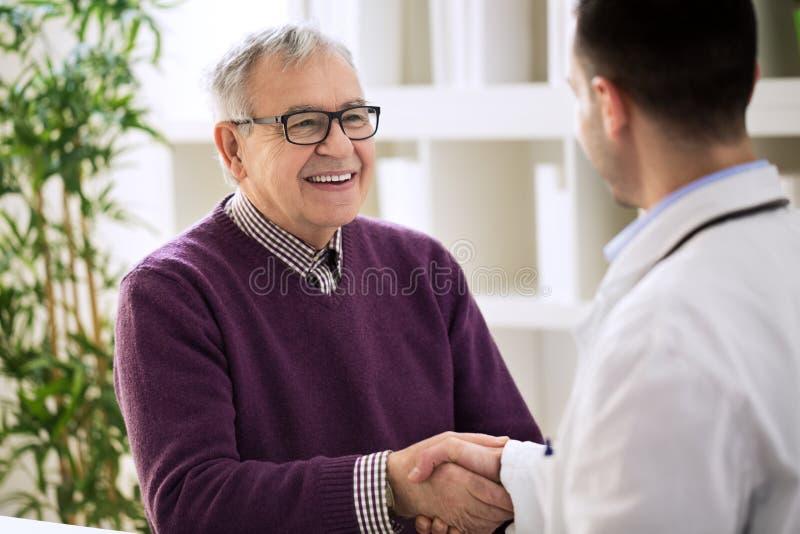Ευτυχές υγιές παλαιό αρσενικό τίναγμα χαμόγελου με το γιατρό στοκ εικόνα με δικαίωμα ελεύθερης χρήσης