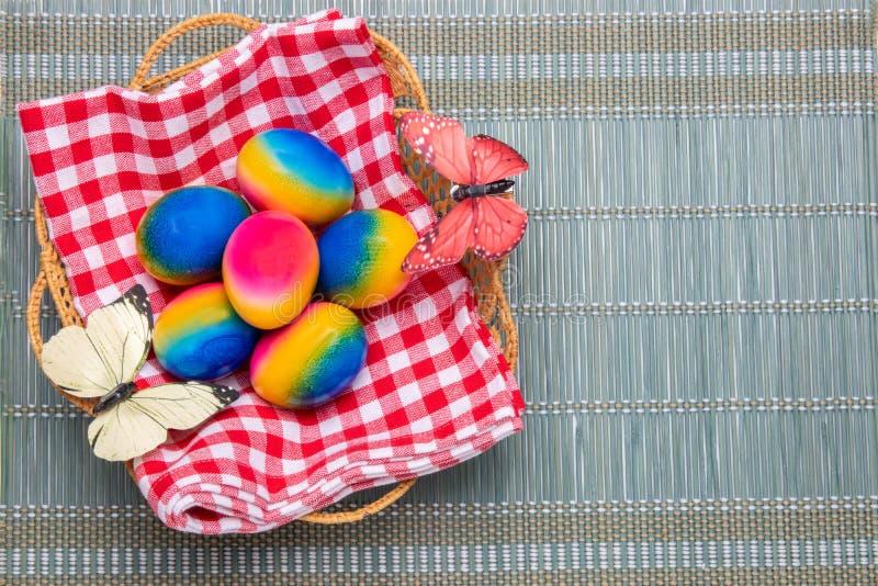 Ευτυχές υπόβαθρο Πάσχας Τοπ άποψη των ζωηρόχρωμων αυγών Πάσχας σε ένα καλάθι στην κόκκινη ελεγμένη πετσέτα σε ένα πράσινο χαλί μπ στοκ εικόνες με δικαίωμα ελεύθερης χρήσης
