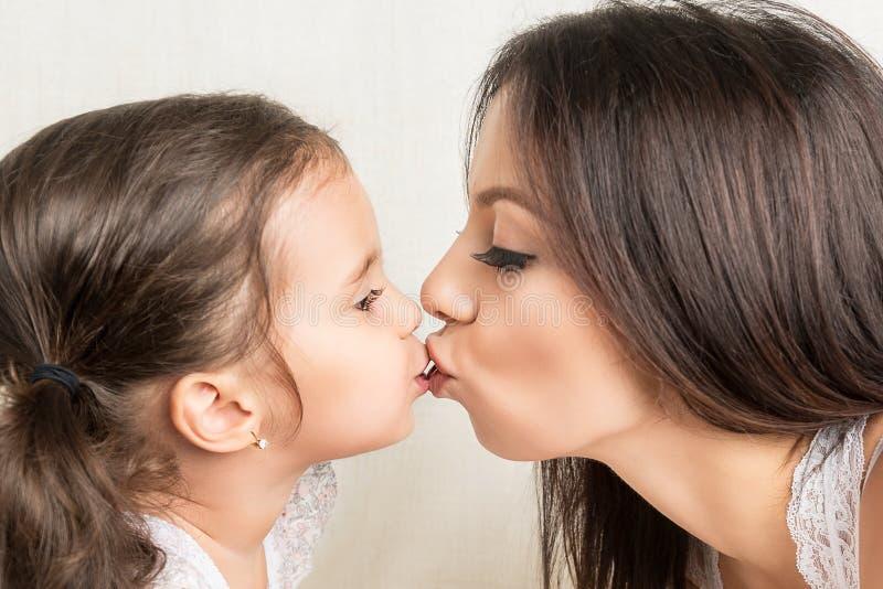 Ευτυχές φίλημα μητέρων και κορών στοκ φωτογραφία