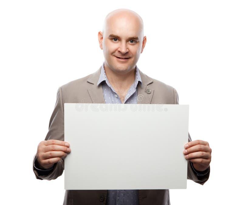Ευτυχές φαλακρό άτομο που παρουσιάζει και που επιδεικνύει αφίσσα έτοιμη για το κείμενο ή το προϊόν σας στοκ εικόνες