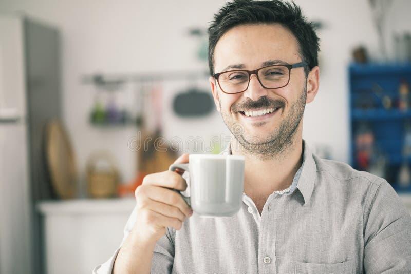 Ευτυχές χαμογελώντας άτομο που φαίνεται κάμερα και που έχει το φλιτζάνι του καφέ στοκ φωτογραφίες
