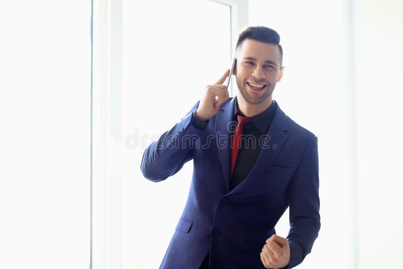 Ευτυχές χαμογελώντας επιχειρησιακό άτομο που μιλά στο τηλέφωνο κυττάρων στο γραφείο στοκ φωτογραφίες με δικαίωμα ελεύθερης χρήσης