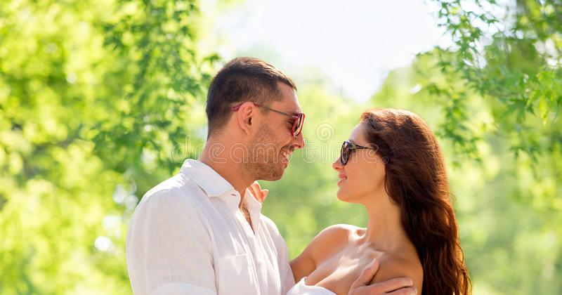 Ευτυχές χαμογελώντας ζεύγος στο αγκάλιασμα γυαλιών ηλίου στοκ εικόνες