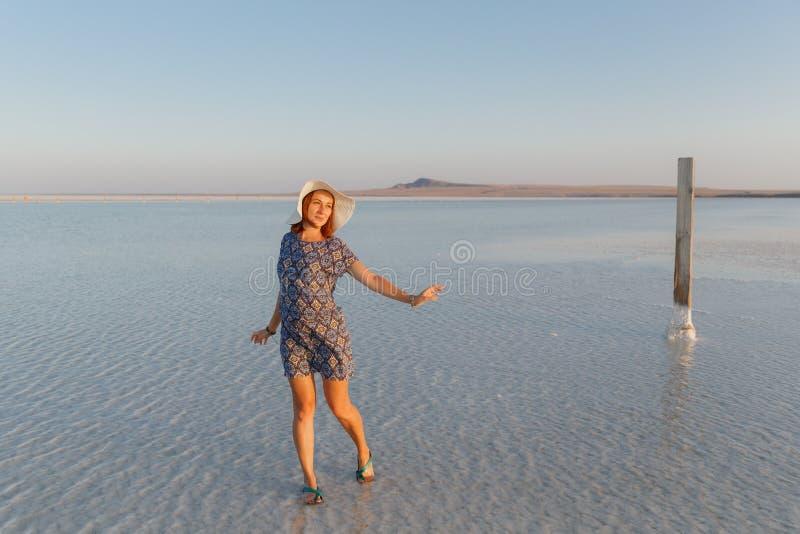 Ευτυχές χαμογελώντας κορίτσι που απολαμβάνει το ηλιοβασίλεμα, που χορεύει στο νερό της αλατισμένης λίμνης Bascunchak στοκ εικόνα