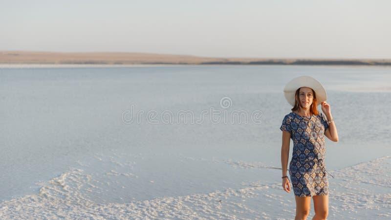 Ευτυχές χαμογελώντας κορίτσι στο άσπρο καπέλο που απολαμβάνει τον ήλιο, έκταση της αλατισμένης λίμνης Bascunchak στοκ εικόνες