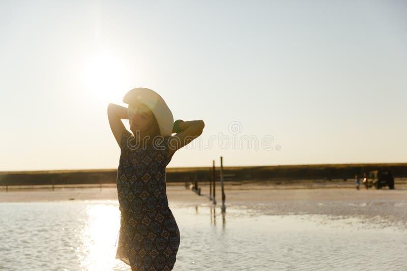 Ευτυχές χαμογελώντας κορίτσι στο άσπρο καπέλο που απολαμβάνει τον ήλιο, έκταση της αλατισμένης λίμνης Bascunchak στοκ φωτογραφία με δικαίωμα ελεύθερης χρήσης