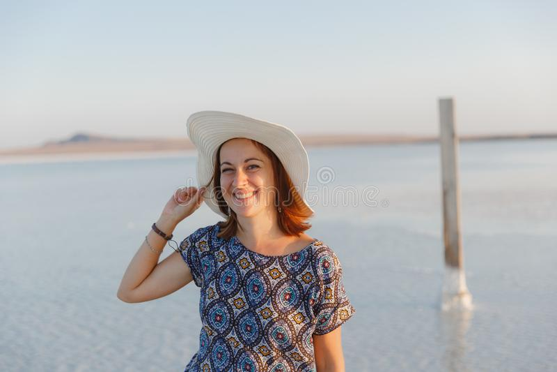 Ευτυχές χαμογελώντας κορίτσι στο άσπρο καπέλο που απολαμβάνει τον ήλιο, έκταση της αλατισμένης λίμνης Bascunchak στοκ εικόνα με δικαίωμα ελεύθερης χρήσης