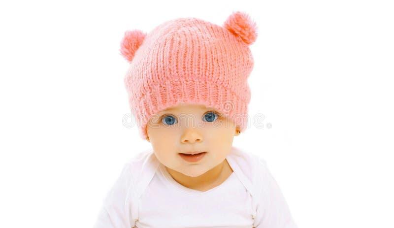 Ευτυχές χαμογελώντας μωρό κινηματογραφήσεων σε πρώτο πλάνο πορτρέτου στο πλεκτό ρόδινο καπέλο στο λευκό στοκ εικόνα