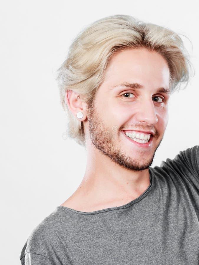 Ευτυχές χαμογελώντας ξανθό άτομο στην γκρίζα μπλούζα στοκ φωτογραφία με δικαίωμα ελεύθερης χρήσης
