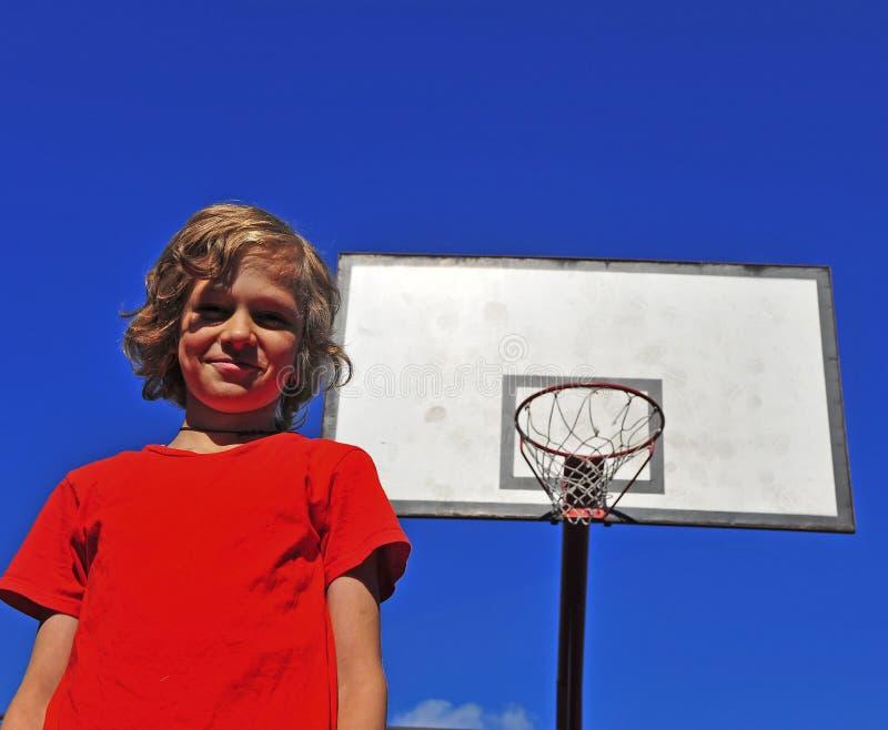 Ευτυχές χαμογελώντας αγόρι με τη στεφάνη καλαθοσφαίρισης στο υπόβαθρο στοκ εικόνα