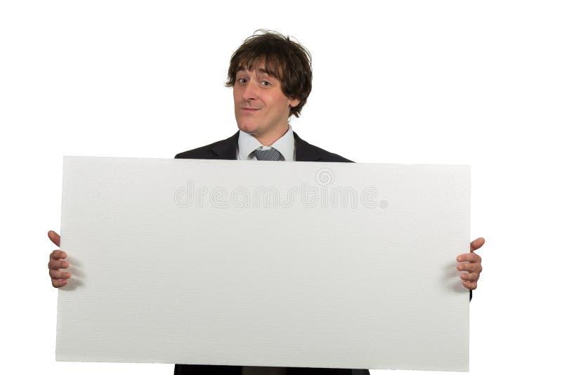 Ευτυχές χαμογελώντας επιχειρησιακό άτομο που παρουσιάζει κενή πινακίδα, που απομονώνεται πέρα από το άσπρο υπόβαθρο στοκ εικόνα