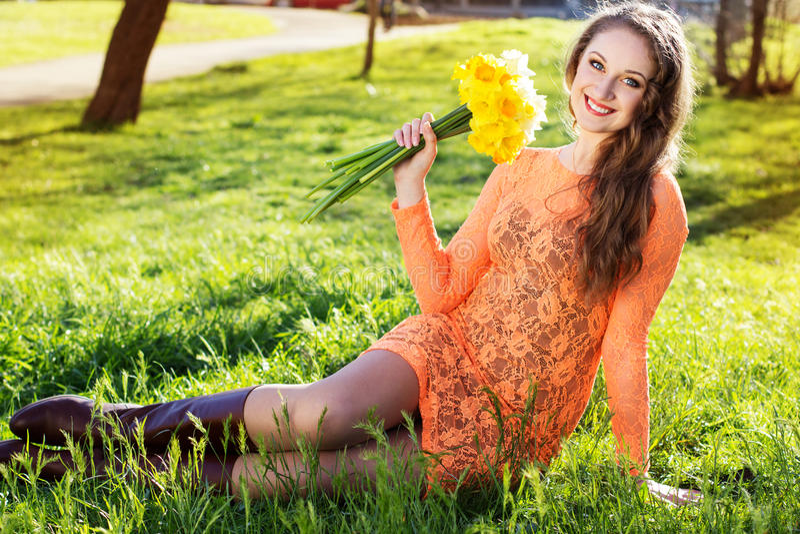 Ευτυχές χαμογελώντας κορίτσι με τα κίτρινα λουλούδια στοκ εικόνες