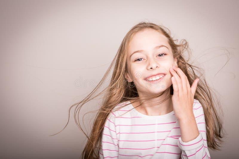 Ευτυχές χαμογελώντας κορίτσι παιδιών με την όμορφη μακριά ξανθή ευθεία τρίχα στοκ φωτογραφία