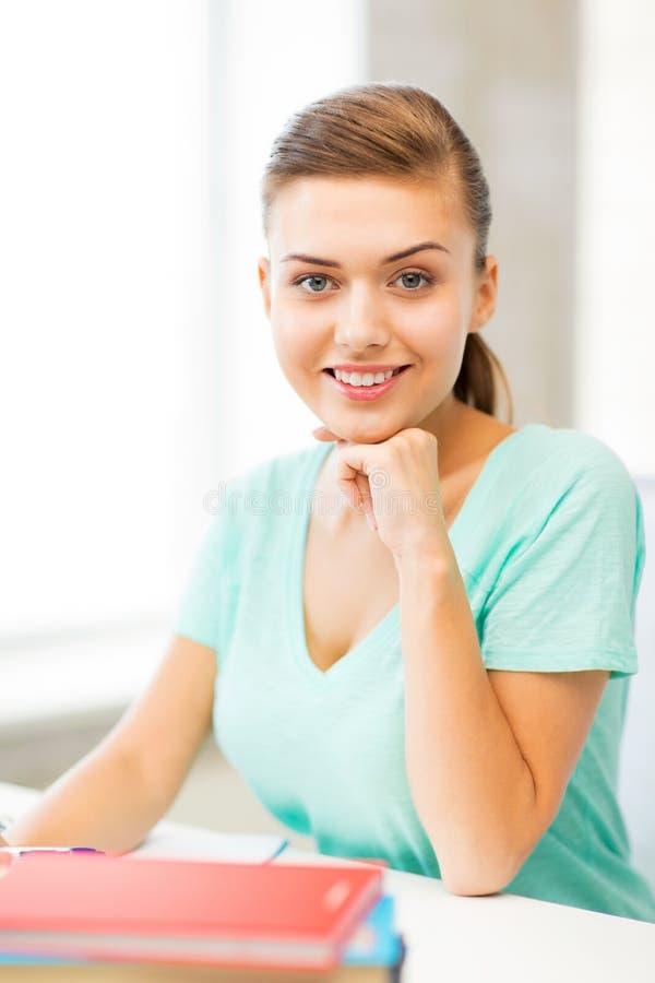 Ευτυχές χαμογελώντας κορίτσι σπουδαστών με τα βιβλία στοκ εικόνες