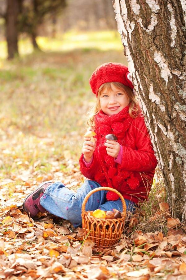 Ευτυχές χαμογελώντας μικρό κορίτσι με τα μανιτάρια στοκ φωτογραφία