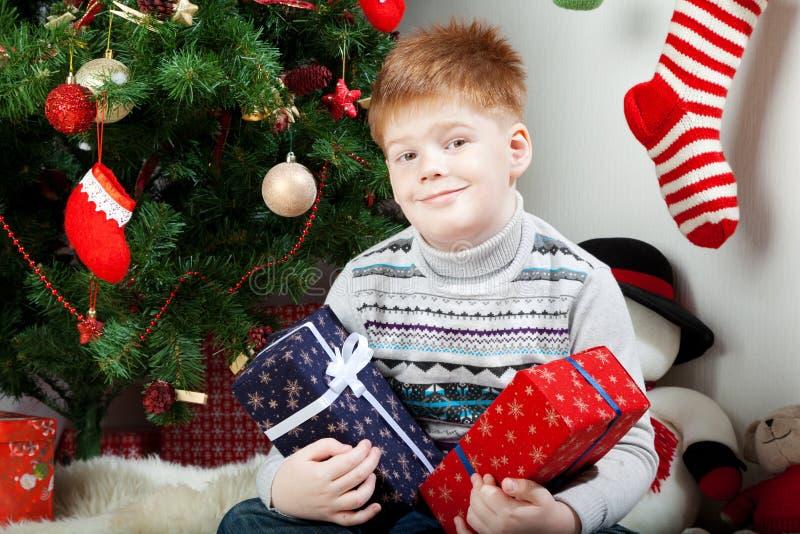 Ευτυχές χαμογελώντας μικρό παιδί με τα κιβώτια δώρων Χριστουγέννων στοκ φωτογραφίες