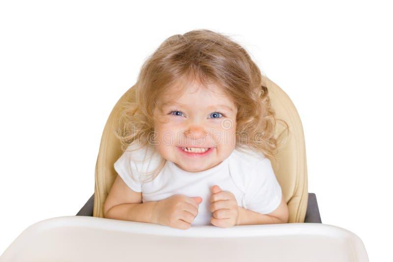Ευτυχές χαμογελώντας μωρό στην υψηλή καρέκλα Απομονωμένος στο λευκό στοκ φωτογραφία