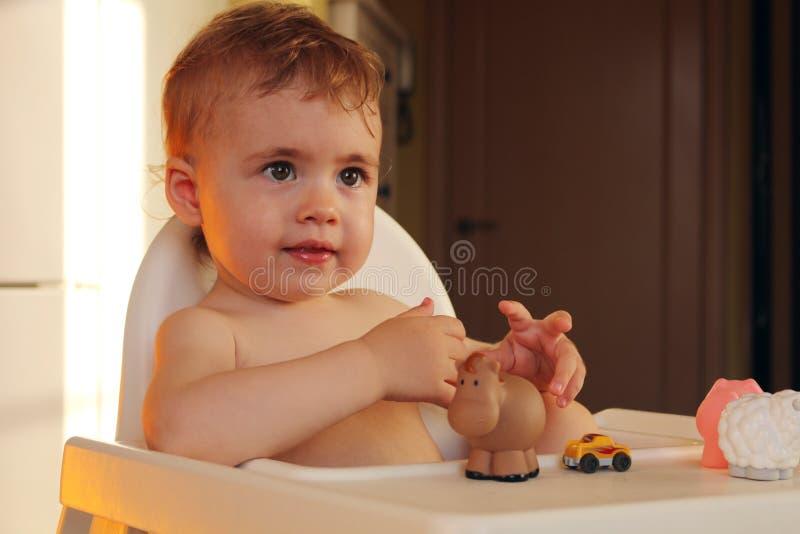 Ευτυχές χαμογελώντας μωρό στην υψηλή καρέκλα στοκ φωτογραφίες