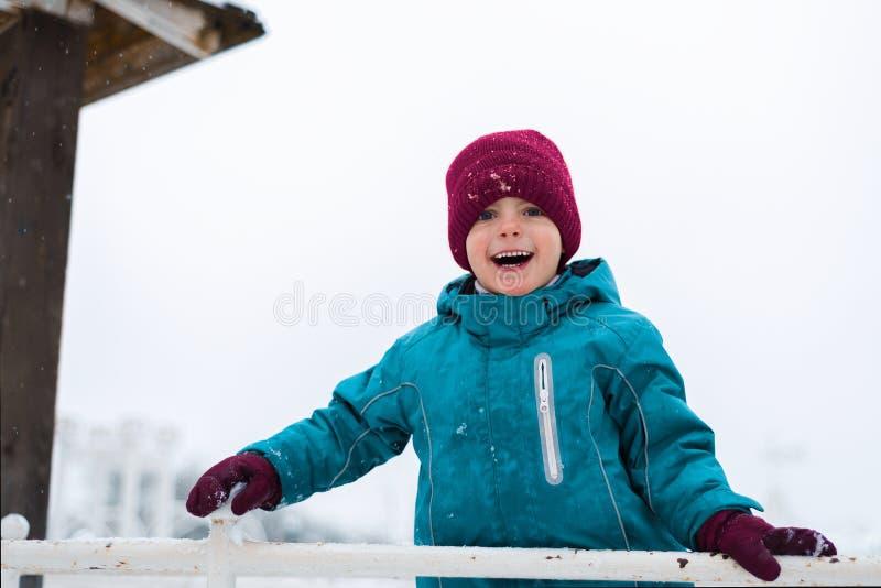 ευτυχές χαμόγελο μωρών παιχνίδια αγοριών το χειμώνα στην παιδική χαρά το παιδί φορά ένα κόκκινη καπέλο, μια μπλε ζακέτα και τα γά στοκ εικόνες με δικαίωμα ελεύθερης χρήσης