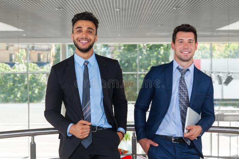 Ευτυχές χαμόγελο ατόμων δύο επιχειρήσεων που στέκεται στο σύγχρονο γραφείο στοκ εικόνα