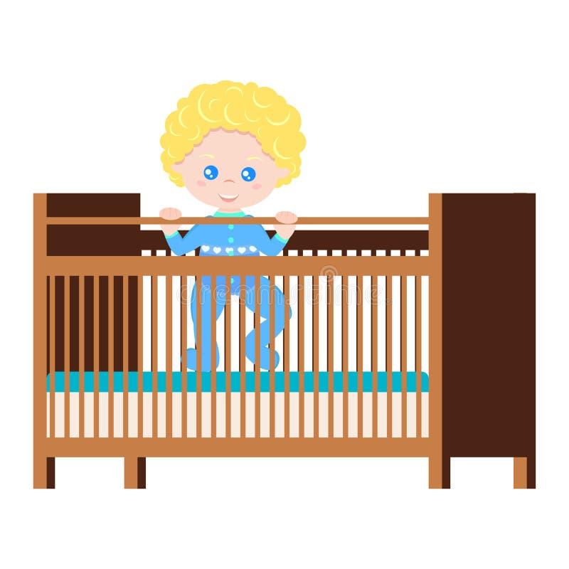 Ευτυχές χαριτωμένο αγοράκι στο μπλε κοστούμι σωμάτων πιτζαμάτων που στέκεται στο ξύλινο παχνί με το στρώμα δύο ελεύθερη απεικόνιση δικαιώματος