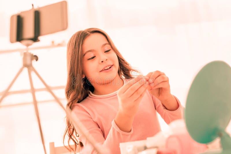 Ευτυχές χαριτωμένο ευχαριστημένο κορίτσι που εξετάζει το δαχτυλίδι στοκ εικόνα
