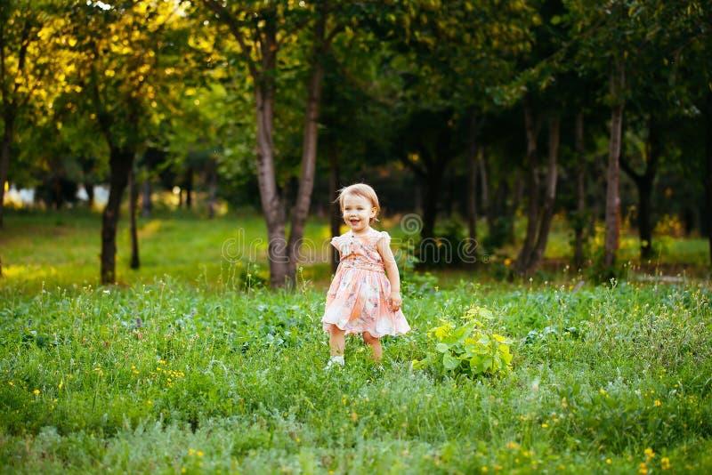 Ευτυχές χαριτωμένο μικρό κορίτσι που τρέχει στη χλόη στο πάρκο Ευτυχία στοκ εικόνες