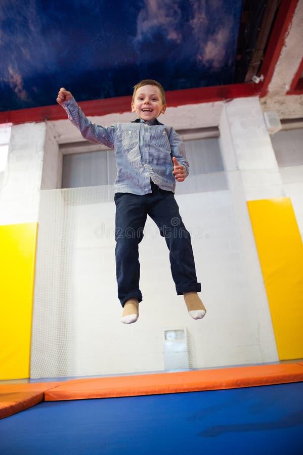 Ευτυχές χαριτωμένο μικρό παιδί που πηδά σε ένα τραμπολίνο στο εσωτερικό στοκ εικόνα