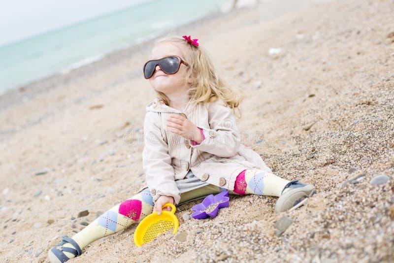 Ευτυχές χαριτωμένο παιχνίδι μικρών κοριτσιών στην παραλία στοκ εικόνες