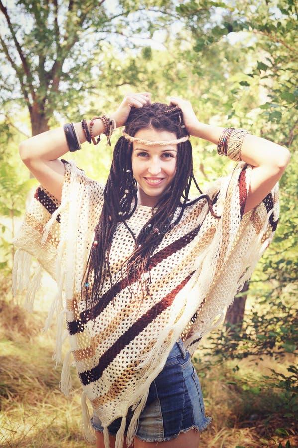 Ευτυχές χαρούμενο υπαίθριο πορτρέτο γυναικών ύφους boho, που ντύνεται πλεκτά poncho και headband, που θέτουν τα χέρια επάνω ενάντ στοκ εικόνες