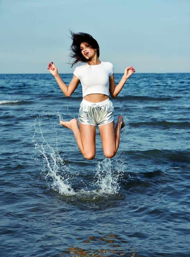 Ευτυχές όμορφο άλμα κοριτσιών στο θαλάσσιο νερό στοκ εικόνα