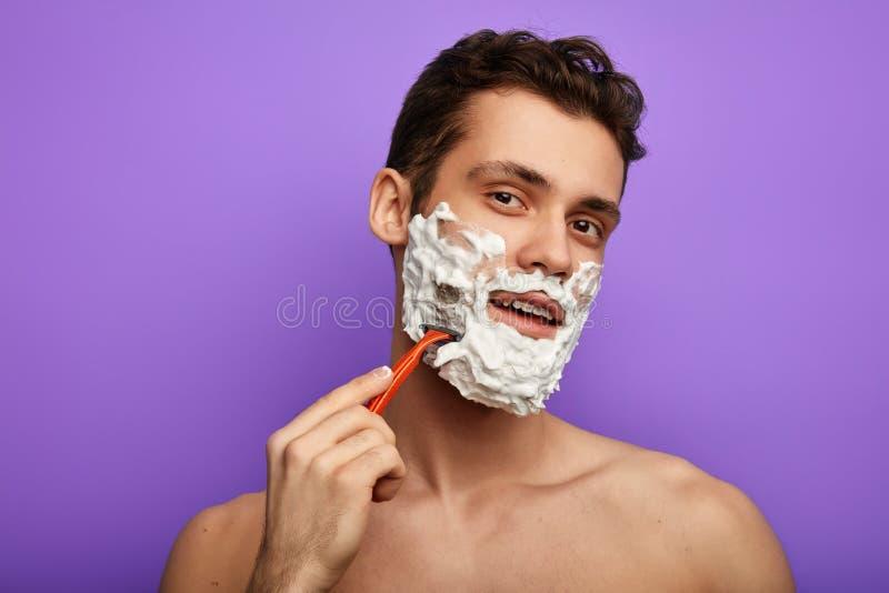 Ευτυχές όμορφο άτομο που εξετάζει τη κάμερα και που ξυρίζει το πρόσωπό του με το ξυράφι στοκ εικόνα