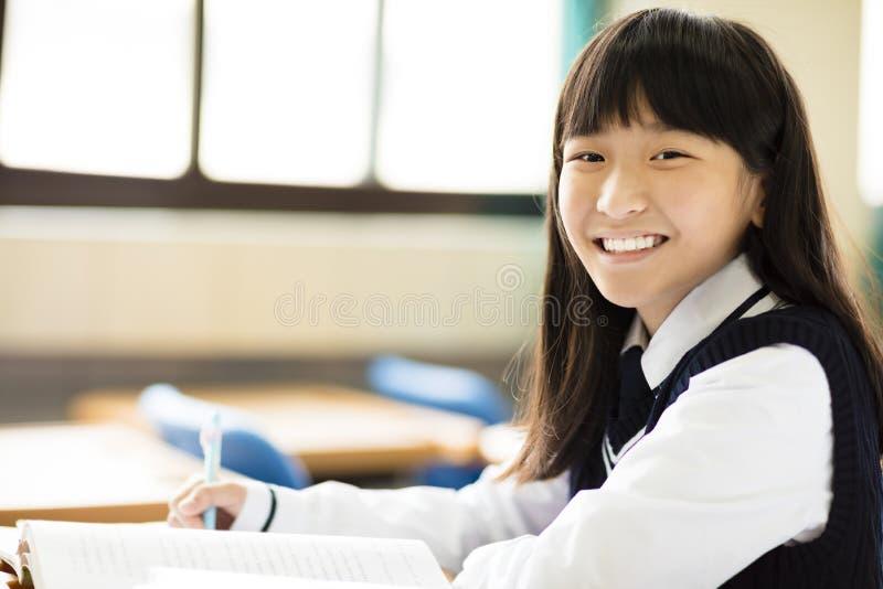 Ευτυχές όμορφο κορίτσι σπουδαστών με τα βιβλία στην τάξη στοκ φωτογραφία